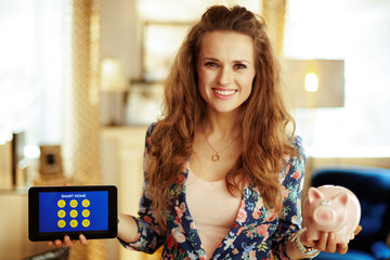 woman showing tablet PC with smart home application and piggy ba