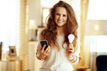 happy housewife with smartphone and smart lamp in modern house