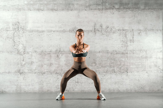 Muscular brunette with ponytail and in sportswear doing squat endurance in front of gray wall in gym.