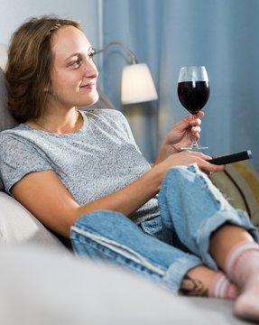 Woman relaxing at home watching TV
