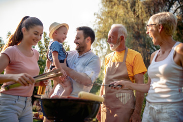 Happy family barbecuing meat on the grill