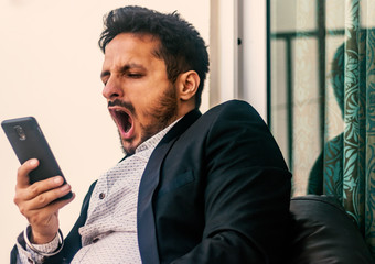 bored man holding smart phone and yawns, front view- image