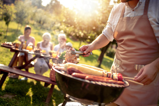 Man preparing food on garden barbecue