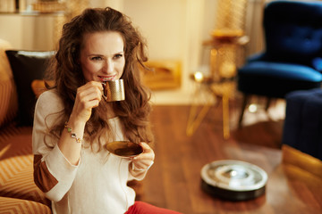 smiling woman drinking coffee while robot vacuum cleaning floor