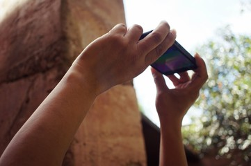 Hand of Asian man use 2 hands to holding smartphone to take photo above his head