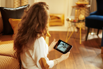 fit woman watching video from security camera on tablet PC