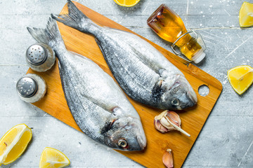 Raw sea fish with lemon wedges and garlic.