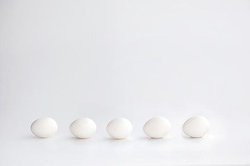 white chicken eggs lined up horizontally on a white background