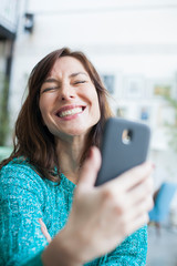 portrait of a woman taking selfie with smartphone