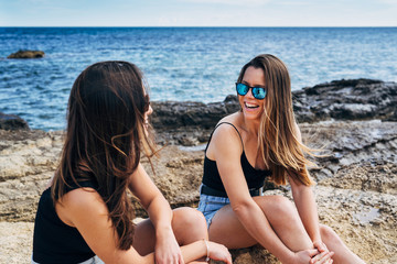 Two young women sitting on the seashore enjoying the summer holidays in the beach