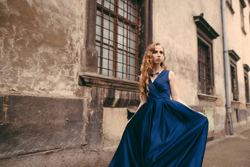 Young beautiful blonde woman in gorgeous blue long dress walking the street near the old building in the old city.