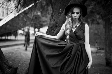 Black and white shot of young woman in long blue dress posing under the tree in the park.