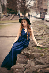 Gorgeous young blonde woman in lond blue dress and black hat sitting on the stony surface in the park. Vintage look
