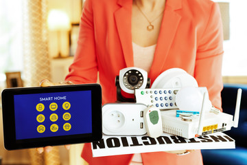 Closeup on smart home devices and tablet PC in hands of woman