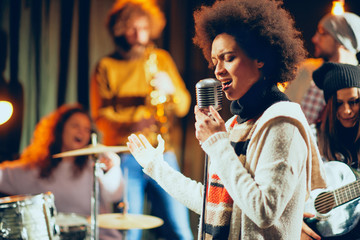 Mixed race woman singing. In background band playing instruments. Home studio interior.