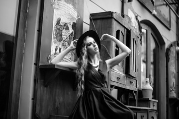 Gorgeous young woman in long blue dress posing in the outdoor cafe with the vintage exterior. Wooden furniture. Black and white shot