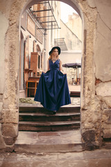 Beautiful blonde woman in gorgeous blue dress and hat walking under arch of the old building in the old city. Vintage shot concept.