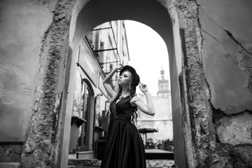 Black and white shot of beautiful blonde woman in gorgeous blue dress and hat walking under arch of the old building in the old city. Vintage shot concept.