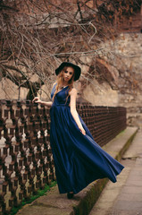 Beautiful young blonde woman in gorgeous long blue dress and hat standing near the fence in the city street.