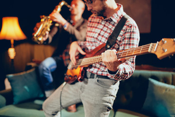 Young Caucasian man with hat on head playing bass guitar while standing in home studio. In background saxophonist playing his instrument.