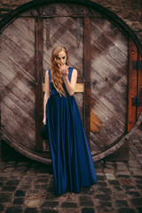Young beautiful blonde woman in long blue dress posing in the old city street near the big wooden barrel