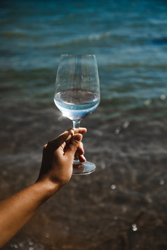 blue sea background wine glass with brilliant liquid natural light tanned female hand