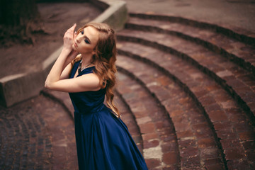 Side portrait of beautiful young blonde woman with gorgeous make up, necklace in blue dress posing outdoors in the street