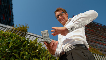 BOTTOM UP: Happy Caucasian businessman throwing hundred dollar banknotes in air.