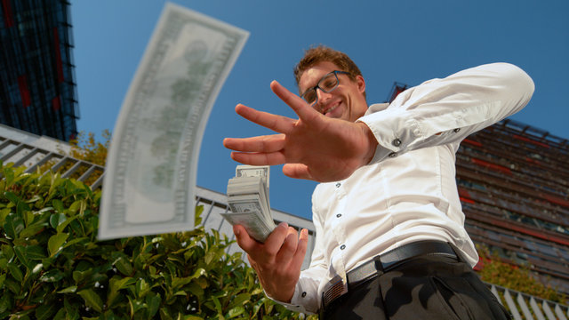 CLOSE UP: Businessman celebrates getting his first paycheck by making it rain.