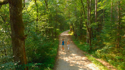 AERIAL: Flying behind unrecognizable fit couple jogging down the forest trail.