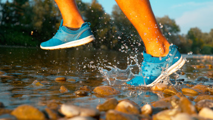 CLOSE UP: Athletic young man running in refreshing glassy stream on a sunny day