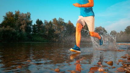 LOW ANGLE: Glassy water droplets fly towards camera as jogger runs in the stream