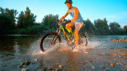 CLOSE UP: Cheerful mountain biker riding in the stream and splashing water.