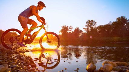 LENS FLARE: Cinematic shot of mountain biker riding across a river at sunset. Wall mural
