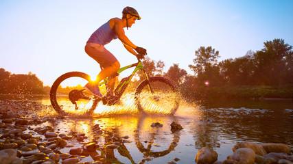 SUN FLARE: Sportsman riding a bicycle through shallow stream on idyllic morning