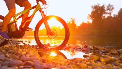 LENS FLARE: Unrecognizable cross country cyclist splashes the river water.