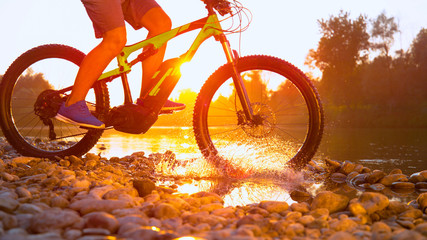 TIME REMAP: Cool shot of mountain biker riding across a river on golden morning.
