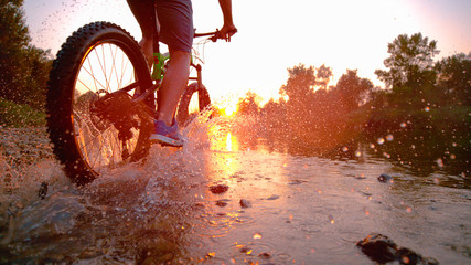 LENS FLARE: Sportsman riding his bicycle in the shallow stream towards sunset. Wall mural
