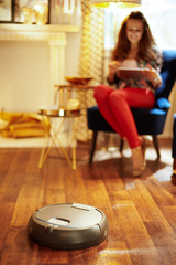 Closeup on robot vacuum cleaning floor while woman relaxing