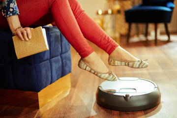 Closeup on robot vacuum cleaning floor and woman rising legs