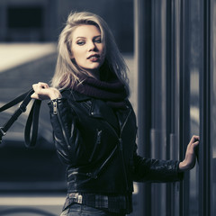 Young fashion blonde woman in leather jacket at the mall door