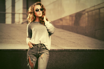 Happy young fashion woman in sunglasses walking on city street