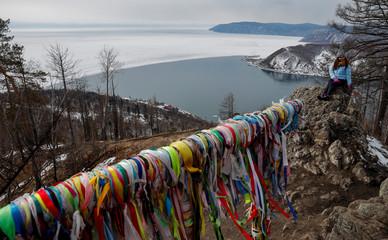 A woman poses for a photo on a hill at the Lake Baikal near the Siberian village of Listvyanka