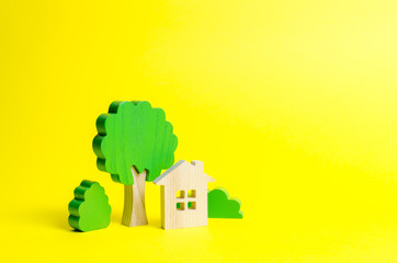 Large two-story house surrounded by bushes and trees on an yellow background. Urbanism and urban landscaping. Acquisition of affordable housing in a mortgage. Accommodation for families.