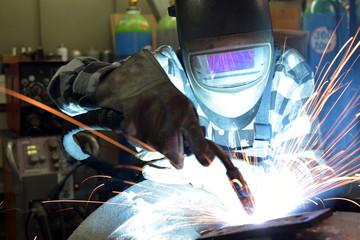 Schweißer im Stahlbau mit Schutzhelm bei der Arbeit // Welder in steel construction with safety helmet at work