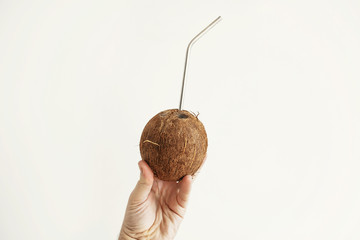 Hand holding coconut with metal straw on white background. Hello summer vacation concept. Zero waste, sustainable lifestyle on tropical island. Copy space. Ban plastic, ecological problem