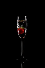Strawberry dropped from the top to wine glass on black background with reflection - image