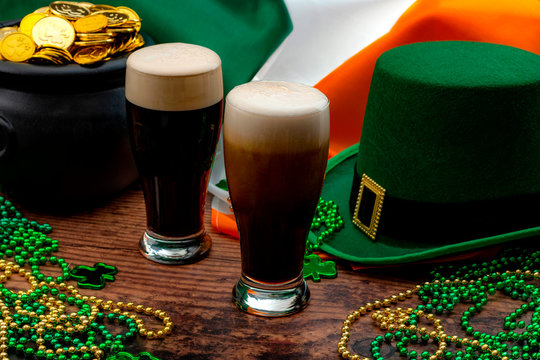 St Patricks day party and Irish celebration of patron saint concept theme with frothy glasses of dry stout, green hat with a buckle, a pot of gold, the flag of Ireland and beads with shamrock in a pub