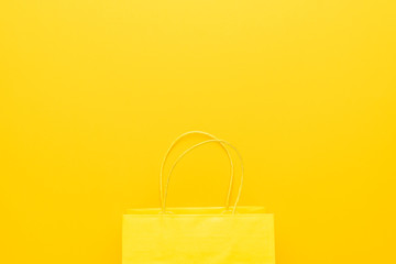 shopping paper bag on the yellow background with copy space. flat lay photo of yellow bag. summer sale concept