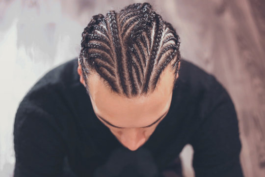 male hairstyle close-up braids, hair braided, pensive look, man portrait
